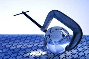 Glass globe being held by C clamp on blue background with money