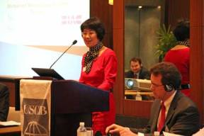 Jianmei Feng of General Electric, co-chair of USCIB's China Committee, addresses the Green Economies Dialogue session; USCIB President and CEO Peter Robinson is at right.